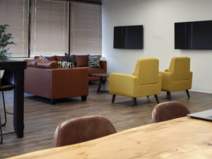 Open concept office space with a few leather chairs, couches and tv's